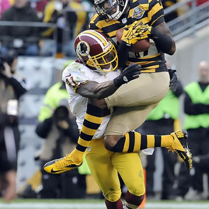 Wallace and Williams The Steelers' Mike Wallace pulls in a catch as he's defended by the Redskins' Madieu Williams in the first quarter.