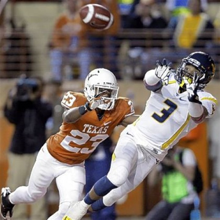 WVU vs. Texas West Virginia's Stedman Bailey leaps for a touchdown pass as Texas' Carrington Byndom defends during the third quarter.