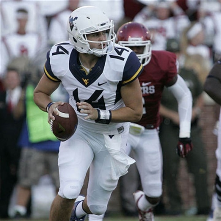wvu2 WVU quarterback Paul Millard looks to throw under pressure Saturday against Oklahoma.