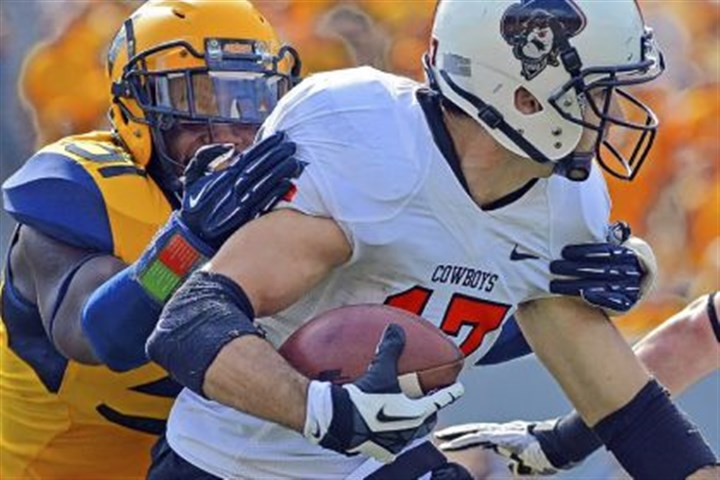 wvu2 Oklahoma State receiver Charlie Moore, right, is brought down by West Virginia defender Isaiah Bruce in the third quarter Saturday in Morgantown, W.Va.
