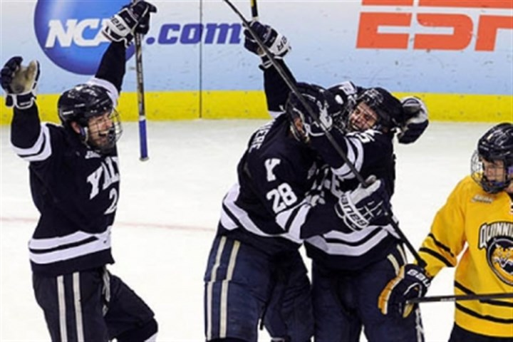 Yalecelebrates After playing nearly two periods with the score, 0-0, Yale's Clinton Bourbonais, second from right, scored for Yale. He is congratulated by teammates Gus Young, left, and Antoine Laganiere. The Bulldogs went onto win, 4-0, at Consol Energy Center for their first NCAA hockey championship.