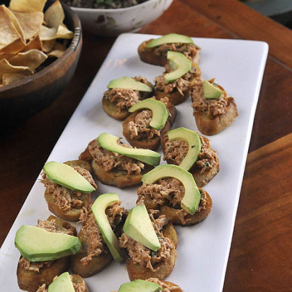 Crab salad topped with avocado slices Crab salad topped with avocado slices. The base is a fried crouton made from a French baugette.