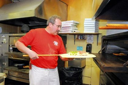 Dominic Mineo Dominic Mineo puts a pizza in the oven at Mineo's, a Squirrel Hill institution that is expanding by 40 seats.