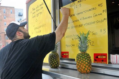 James Rich James Rich, owner of PGH Taco Truck, writes out the menu while parked outside Marty's Market in the Strip District.