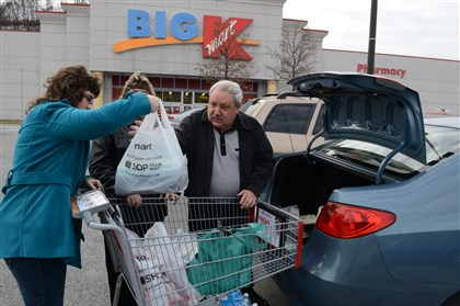 20131128dsKMartLocal Jaime Hoffmann of Elkins, W.Va., and Christine Hinchman and George Caliguri, both of Glassport, unload their bags after shopping in Pleasant Hills. K-Mart stores opened at 6 a.m. on Thanksgiving morning.