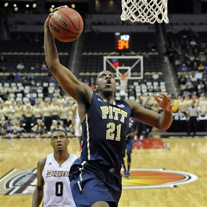 20131130mfpittsports11-10 Pitt's Lamar Patterson drives to the net in front of Duquesne's Ovie Soko in the first half of the City Game at Consol Energy Center Saturday.