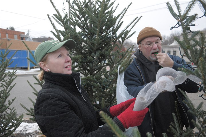 20131130ttDecorateAllZone1 Volunteer Nancy Thomas and Crafton Mayor Jim Bloom decorate a tree on a traffic island opposite the Crafton Borough Building on Stotz Avenue.