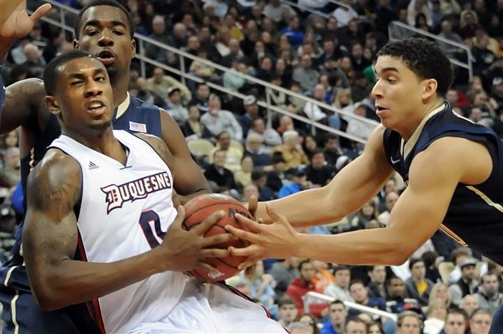 20131130mfpittsports14-13 Pitt's James Robinson reaches for the ball against Duquesne's Ovie Soko in the second half of the City Game at Consol Energy Center Saturday.
