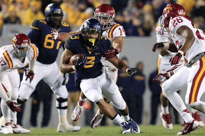 Iowa St West Virginia Football West Virginia running back Charles Sims runs the ball as several Iowa State defenders close in.