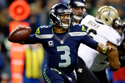 wilson1203-11 Quarterback Russell Wilson of the Seattle Seahawks looks to pass against the New Orleans Saints in a game Monday night at CenturyLink Field in Seattle.