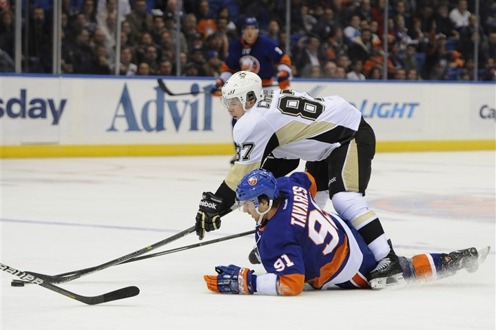 20131203Penguins1 New York Islanders center John Tavares battles with Sidney Crosby for the puck in the second period Tuesday in Uniondale, N.Y.