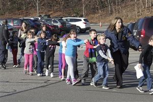 In this photo provided by the Newtown Bee, Connecticut State Police lead children from the Sandy Hook Elementary School in Newtown, Conn., following a shooting there Friday, Dec. 14, 2012.