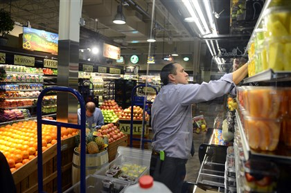 20131204RARbusinessgrocery1 Giant Eagle employee Bryan Gillette stocks the produce department in preparation for the opening of the new Market District Express in Peters.