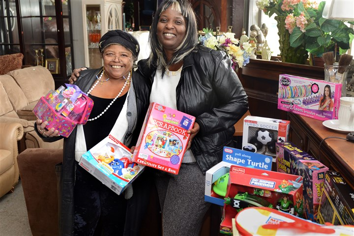 20131204goodfellowtoys Bishop Osceola Sanders and Tammy Kabba pose Wednesday with some of the toys they collected to give to needy children.