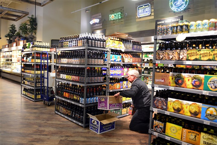 20131204RARbusinessgrocery2-1 Bill Brazel, a beer merchandiser with Giant Eagle, stocks the shelves in the beer department in preparation for the opening of the new Market District Express in Peters.