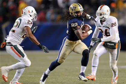 20131129mfpittsports10-4.jpg Pitt's Manasseh Garner carries as he's defended by Miami's Kacy Rodgers II and Kayshawn Jenkins in the fourth quarter at Heinz Field last week.