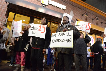 20131205dsSTRIKE02-6 The 6 a.m. rally gets started outside of the Dunkin Donuts shop on Thursday at Market Square, as protesters call for an increase to the federal minimum wage to $15 an hour.
