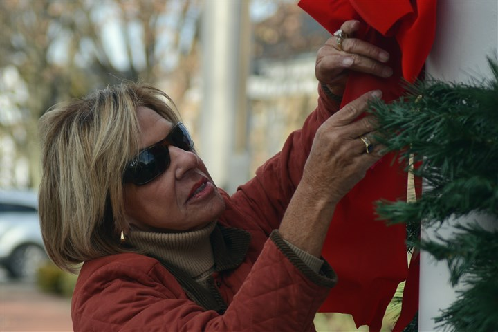 1116mhLigonierXmasWest02-1 Nancy Donchez, a retired teacher from the Ligonier Valley School District, helps to decorate the town square for Christmas.