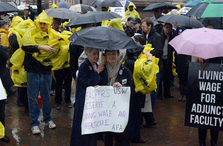 20131205lfProtestLocal02-2 Rae O'Hair, left, a Duquesne University alumna, and her friend Daniele Orosz rally in the rain, protesting the university's opposition to unionizing adjunct faculty on Thursday.
