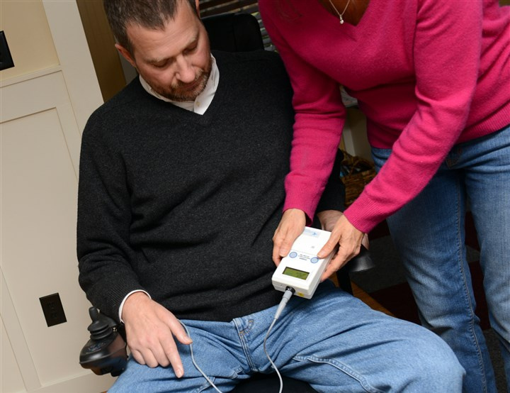 20131204ppAlexander2LOCAL Neil Alexander of O'Hara watches as his wife sets up a diaphragm pacing system he is using in response to the advancing symptoms of ALS.