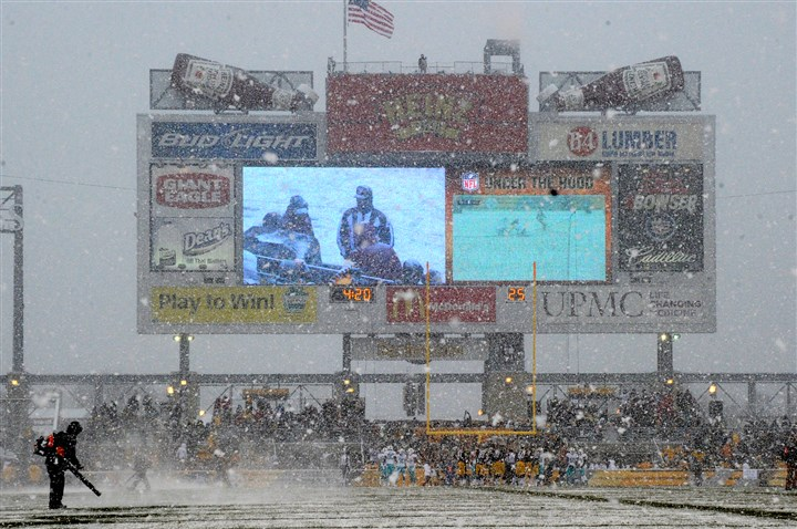 Snowy Heinz Field Grounds crew workers blow snow off the field during a timeout.