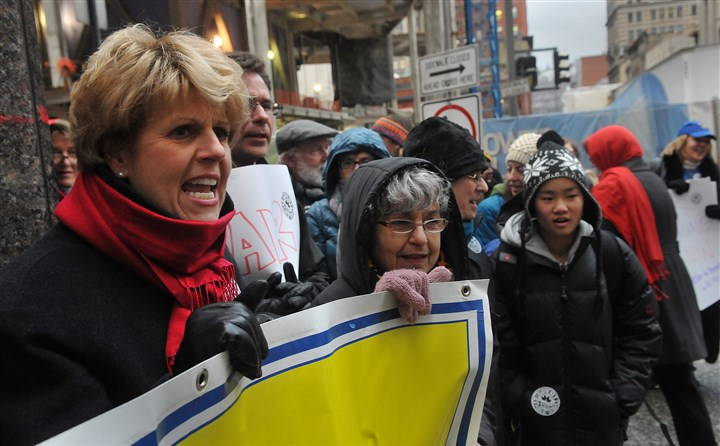 20131209lrteacherslocal04-2 At a rally called by teachers to protest the actions of the Corbett Administration, Deb Dunton, left, a special education teacher at Greenfield Elementary School, chants slogans against the governor with people attending the rally on Monday at Gov. Corbett's office in Pittsburgh at Fifth and Wood streets, Downtown.