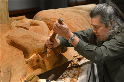 20131204dsTotemPoleMag03 Tommy Joseph, a member of the Tlingit people of southeast Alaska, uses a reverse bent knife to carve a 16-foot totem pole that will be permanently installed at the Carnegie Museum of Natural History.
