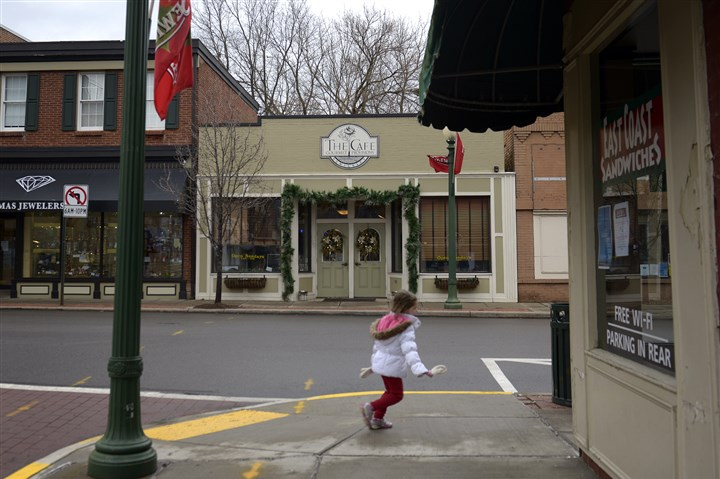 20131209jrDecorZones4-2 A child runs along Beaver Road past the decorated shops in Sewickley.