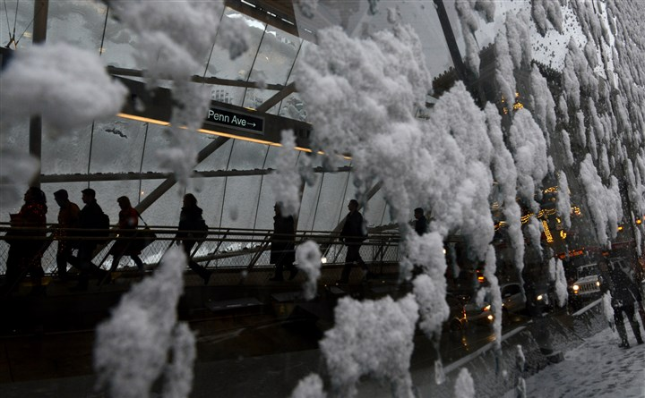 20131210dsSnowLocal03 Snow hangs on the glass atrium atop of the Gateway Station as commuters walk through early Tuesday morning.