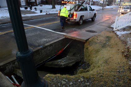 20131212dsPoplarWaterMainLocal01.jpg-1 Outbound traffic was closed because of a water main break, causing the sidewalk to collapse along Poplar Street in Green Tree.