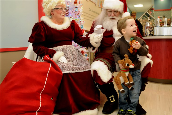 20131201RARzonessanta2-1 Austin Kemerer, 5, of Irwin, is thrilled to receive a small reindeer from Santa and Mrs. Claus that resembles his larger stuffed reindeer. Austin visited with Santa and Mrs. Claus — portrayed by Gary and Colleen Odenthal of Elizabeth Township — Dec. 1 at Sincerely Yogurt in Irwin.
