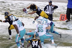 From the archives: Troy Polamalu dives for the end zone after intercepting a pass for a touchdown during the second half of a game against the Miami Dolphins in Pittsburgh, Sunday, Dec. 8, 2013.