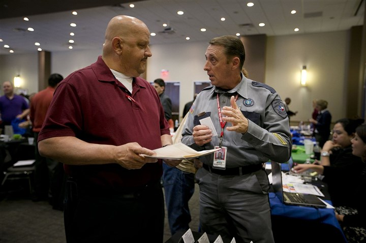 20131204VETERANS2biz Don Ream, a U.S. Army veteran, left, talks with Texas Department of Criminal Justice officer Jeremy Young, at the Hiring Red, White & You! job fair event last month in Austin, Texas.