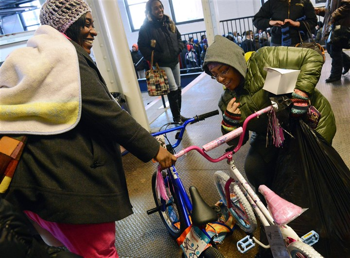 20131212lfToyLocal02-1 Rasheeda Peoples, 36, left, of the North Side and her sister, Fashawna, 34, of Mount Washington pick up bicycles at the Toys for Tots event in the Strip District on Friday.