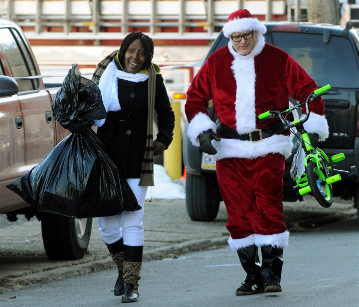 20131212lfToyLocal01 Craig Biertempfel, 43, of Friendship helps Alexis Givner, 27, of Troy Hill carry a bike to her car from a Toys for Tots distribution Friday in the Strip District.