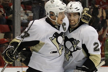 pens1215a Sidney Crosby, left, celebrates with Matt Niskanen after scoring the first of his two goals Saturday night in Detroit.