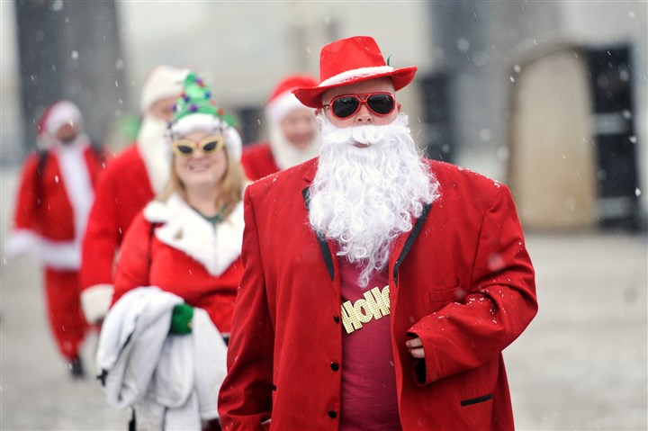 20131214rldSantaConLOCAL04-6 Santa Pimp, a.k.a Jack Ingraham of Shaler, leads a procession of Santas to a water taxi during the annual Santarchy gathering on Saturday. The revelers started on the North Side and continued the festivities Downtown and on the South Side.