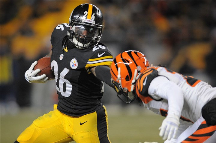 20131215jrSteelers14-2 Le'Veon Bell pushes off Dre Kirkpatrick Sunday night during the Steelers' win against the Cincinnati Bengals at Heinz Field.