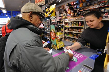 20131216JHLocalLottery02-1 Dave Woods buys lottery tickets at Smithfield News, Downtown, from cashier Amanda Smith before catching his bus for home in the South Hills on Dec 16.