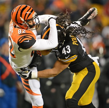 20131215pdSteelersSports06-1 Troy Polamalu defends the Bengals Marvin Jones in the first half Sunday night at Heinz Field.