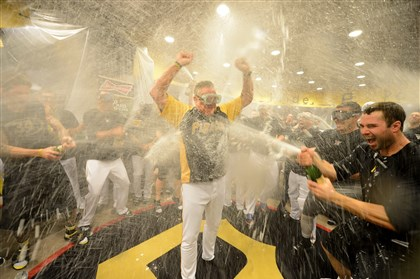 Pirates1222-4 Pirates manager Clint Hurdle celebrates the team's victory in a wild-card game by allowing himself to be the target of champagne blasts Oct. 1.