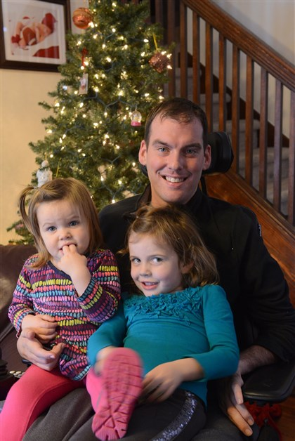 20131217rldOnyshkoLOCAL02-1 Matthew Onyshko with his daughters McKenna, 1, left, and Kendall, 4, at their home in Brighton Heights on Tuesday. Mr. Onyshko, who played football at California University of Pennsylvania, has filed a lawsuit against the NCAA for disabilities that have developed in the years since he played.