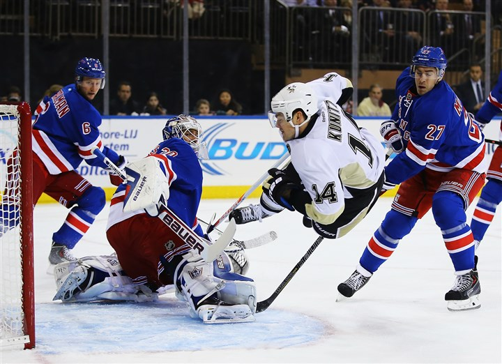 9l900msc Penguins left winger Chris Kunitz falls after shooting against Rangers goalie Henrik Lundqvist during their game at Madison Square Garden in New York City.