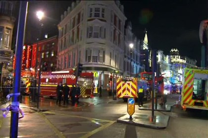 Britain Theater Collapse This image taken from television shows emergency services attending an incident at the Apollo Theatre, illuminated at rear right, on London's Shaftesbury Avenue on Thursday evening. It wasn't immediately clear if the roof, ceiling or balcony collapsed during a performance.