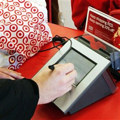 TargetCreditInfo A customer signs his credit card receipt at a Target store in Tallahassee, Fla.