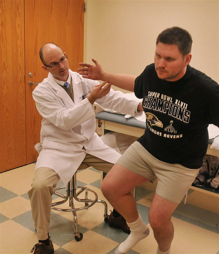 20131209hiphealth07 Dr. John Christoforetti puts Justin Roth, a truck driver from Lancaster, Pa., through a series of tests at West Penn Hospital to see if he could be a candidate for arthroscopic hip surgery.