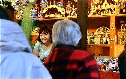 20131222RARlocalshops2-11 Debbie Baird talks to customers while working in the Old German Christmas house at the holiday shops in Market Square on Sunday afternoon.