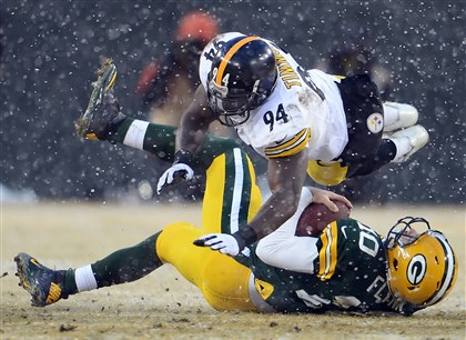 20131222pdSteelersSports05-1 Lawrence Timmons tackles Packers quarterback Matt Flynn in the second quarter yesterday at Green Bay's Lambeau Field.