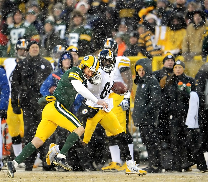 20131222pdSteelersSports06-2 Packers' kicker Mason Crosby knocks Antonio Brown out of bounds in the second quarter Sunday at Lambeau Field.