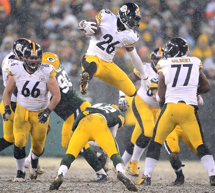 20131222pdSteelersSports09-7 Steelers Le'Veon Bell leaps over Packers Morgan Burnett for first down yardage in the third quarter at Lambeau Field.